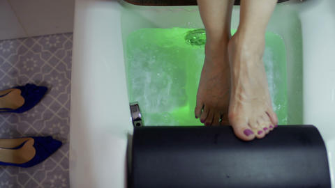 Female relaxing her feet in a small bath with bubbles and colorful lights Footage
