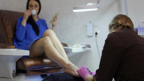 Young woman relaxing in beauty salon during pedicure procedure ภาพวิดีโอ