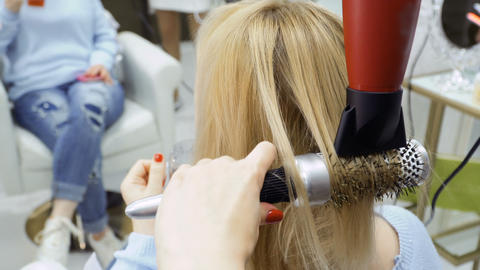 Hairdresser dries female hair with hairdryer and brush Footage