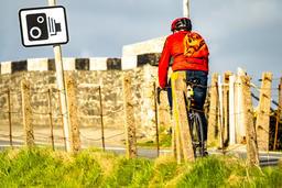 Rear view of a cyclist riding next to radar control sign in the streets in Wales フォト