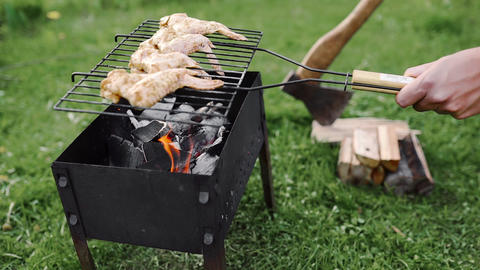 Chef makes BBQ with chicken wings on the hot coals of the grill outdoors 영상물