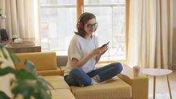 Woman enjoying music on sofa Footage