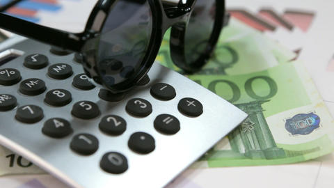 Sun protective hipster glasses lie on the calculator and euros. Rotation Footage