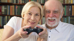 Senior couple gamers playing video game at home. Players with remote controller Footage