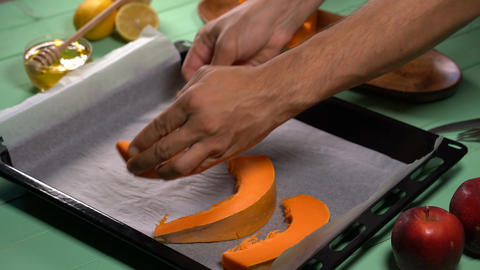 Chef puts slices of pumpkin on a sheet for baking in the oven Footage