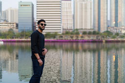 Young handsome Indian man thinking while wearing sunglasses agai フォト