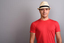 Tourist man wearing hat and red shirt against gray background Photo