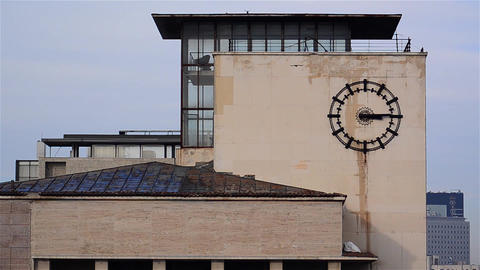 Passage of time marked by metal clock mounted on the wall of a building in downt Footage