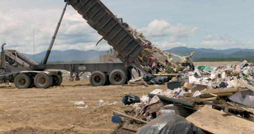 Large dump truck emptying a dumpster of construction and household trash at a Footage