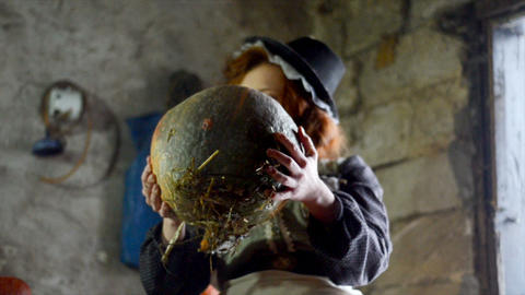 Red-haired girl with a big pumpkin in the hut. Fairy-tale character Footage