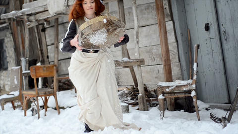 girl in a fairy-tale dress is standing by the old wooden house and throwing snow Footage