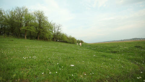 Little girls walking the meadow near the forest GIF