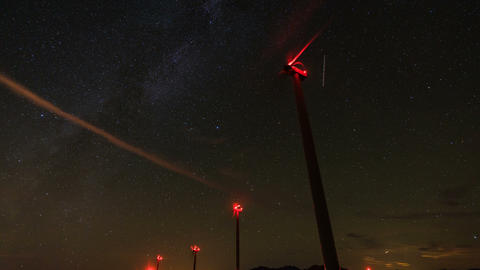 wind turbines generating clean power with milky way ビデオ