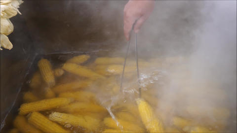 Boiling corns in a large metal pot at the street steaming Footage