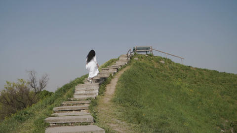 Elegance woman in white long dress moving up the stairs on green hill Footage
