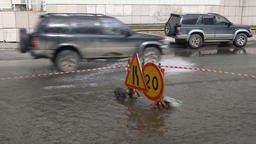 Automobiles driving over deep muddy puddle and splashing water Footage
