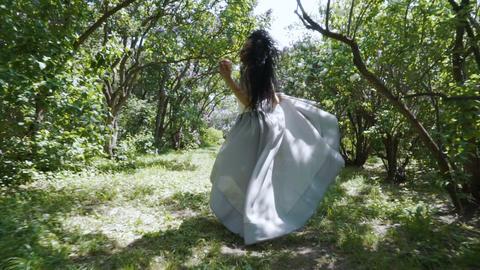 Beautiful woman holding apple in hand run through a garden, Snow White fairytale Footage