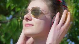 Beautiful teenage girl with headphones enjoys music Footage