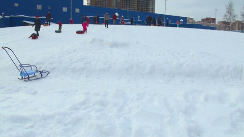 Children go for a drive from a hill in the winter Stock Video Footage
