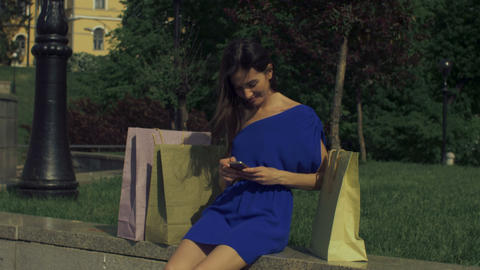 Carefree shopper woman using smart phone in the city GIF