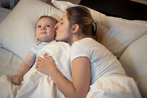 Portrait of loving young mother kissing her baby son before going to sleep フォト