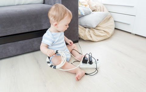 Unatteded little baby boy playing with electric power cables. Child in dangerous Fotografía
