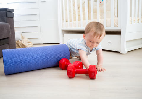 Cute baby boy playing with fitness equipment on floor at home フォト