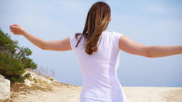Woman jump with joy along sand path. Carefree female raising arms up and dancing Footage