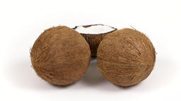 Two whole coconuts and half with yummy pulp rotating on white isolated Footage