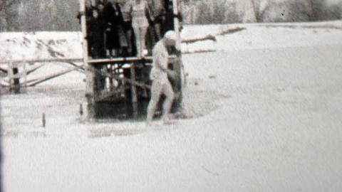 1939: Man jumping polar bear club in frozen lake water runs across ice Footage