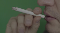 Close-up Of Smoking Cigarette On Green Background stock footage