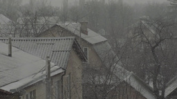 Snow falls on the roofs of houses in the city in winter Footage