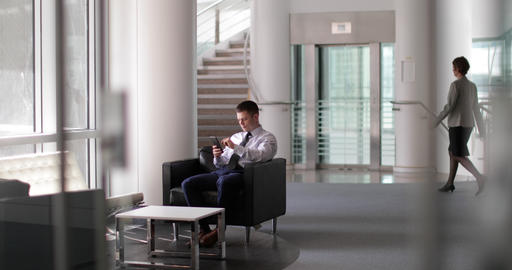 Businessman waiting in office reception using smartphone Footage