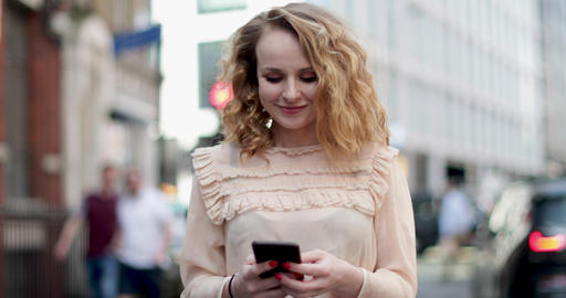 Young adult female looking at smartphone outdoors in city ビデオ