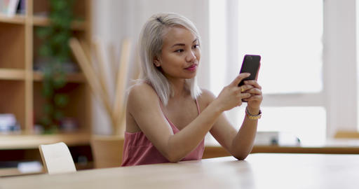 Young adult female using smartphone in college Footage