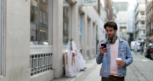 Young adult male walking down street looking at smartphone Footage