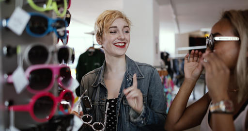 Millennials trying on sunglasses in a vintage store GIF