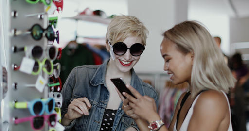 Millennials looking at smartphone in a vintage store Live Action