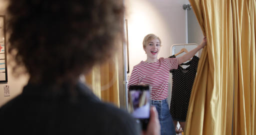 Young adult female trying on clothes in a vintage store with friend Footage