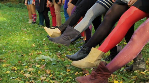 Female legs on grass. Tights of different colors on girls' legs. Girls raise up Live Action
