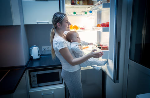 Young mother taking food out of refrigerator at night to cook something for her フォト