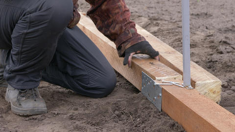 Builder working with electric screwdriver and wooden frame on construction Live Action