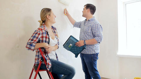 Slow motion footage of young couple painting walls with paint roller at their Footage