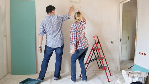Slow motion footage of happy cheerful couple dancing while painting walls Footage