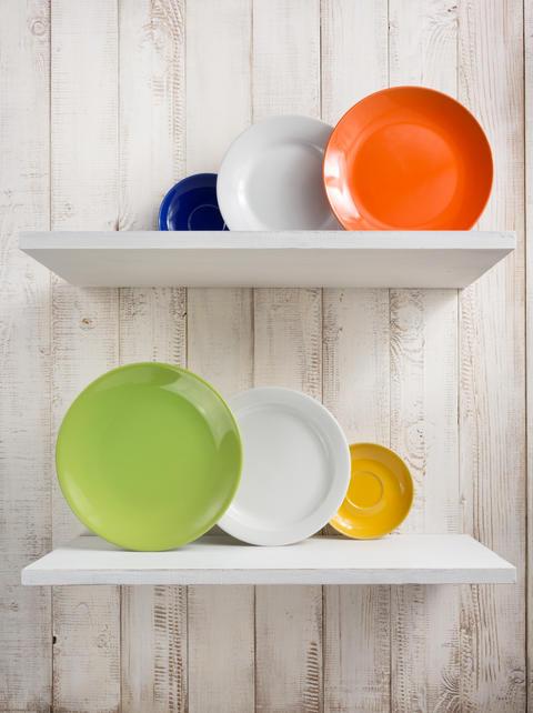 plate at kitchen shelf on wooden background Photo
