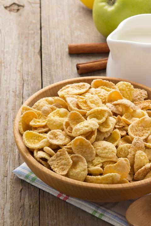 bowl of corn flakes on wood フォト