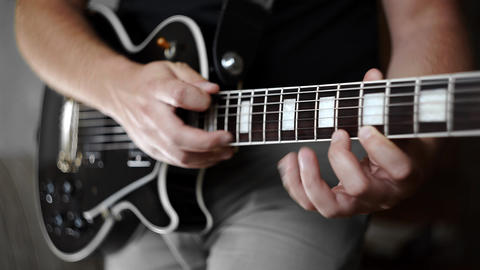 Musician plays solo on the electric guitar and uses tapping, playing on electric Live Action