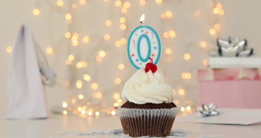 Iced birthday cupcake with with lit number 0 candle Footage