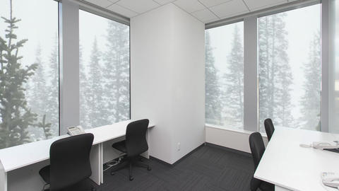 Empty office with chairs and telephones on tables, snowfall in forest outside Footage