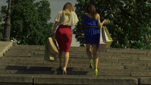 Women with shopping bags going upstairs in city Footage